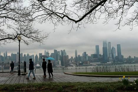 Ihmisiä kävelyllä New Jerseyssä tiistaina. Taustalla New Yorkin pilvenpiirtäjiä.
