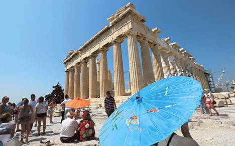 Turistit suojautuivat aurinkovarjoilla paahtavalta helteeltä Ateenan Akropolis-kukkulalla kesäkuussa.