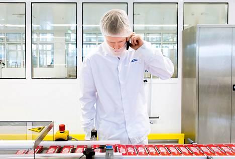 Matti Hirvonen säätää lääkkeiden pakkauslinjaa uudessa tehtaassa. Kännykällä saa yhteyden seinän takana työskentelevään kollegaan.