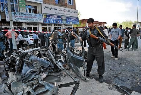 Afganistanilaispoliisi siivoaa itsemurhaiskussa käytetyn auton jäänteitä kadulta Kabulissa maanantaina.