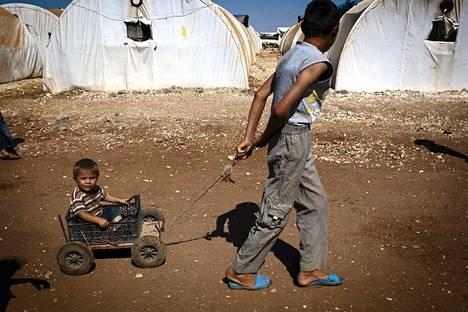 Syyrialainen poika veti pikkuveljeään kärryillä Bab al-Salamin pakolaisleirillä lähellä Turkin rajaa.