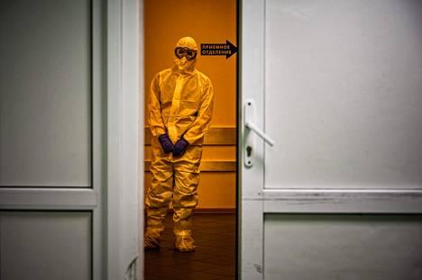 Suoja-asuun pukeutunut hoitohenkilökunnan jäsen seisoi Vinogradovin sairaalan käytävällä Moskovassa sunnuntaina.