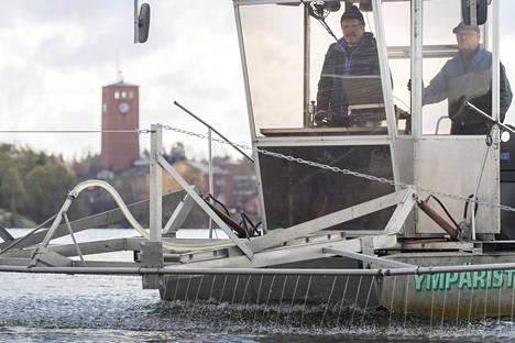 Juha Ryömä ohjaa kemikaalia ruiskuttavaa venettä Littoistenjärvellä. Vieressä Veijo Ojansuu.