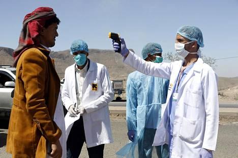Sairaalatyöntekijät tarkistivat miehen ruumiinlämpöä Sanaan kaupungin lähistöllä Jemenissä sunnuntaina.