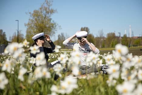 Tänä keväänä valmistuvat Cindy Lindström ja William Wasenius kävivät ostamassa itselleen ylioppilaslakit, joita sovittivat piknikillä Töölönlahdenpuistossa.