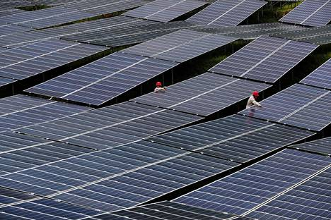 Kiinalaiset työntekijät huolsivat aurinkopaneeleita aurinkovoimalassa Chongqingissä viime heinäkuussa.