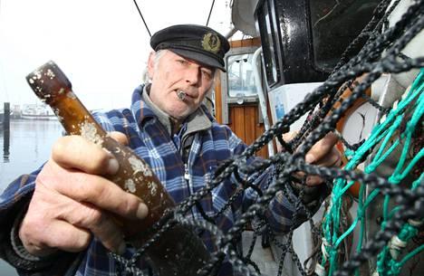 Saksalainen kalastaja Konrad Fischer pitelee kädessään pulloa, jonka viesti on kirjoitettu vuonna 1913.