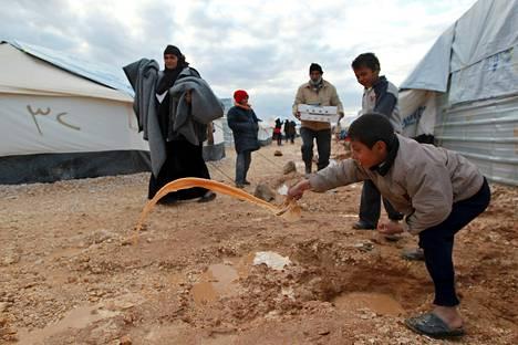 Syyrialaispakolaiset äyskäröivät vettä telttansa ympäriltä Mafraqin pakolaisleirillä Jordaniassa kaksi viikkoa sitten.