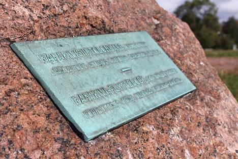 Laatta kertoo Kaivopuiston rapakivisiirtolohkareen suojelusta.