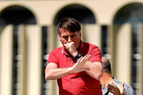 Presidentti Jair Bolsonaro yski nyrkkiinsä puhuessaan mielenosoittajille Brasíliassa sunnuntaina.