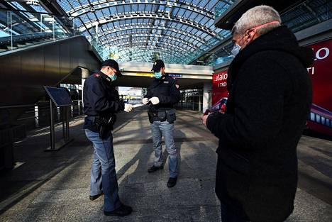 Poliisit tarkastivat junamatkustajan asiakirjoja Torinon rautatieasemalla tiistaina.