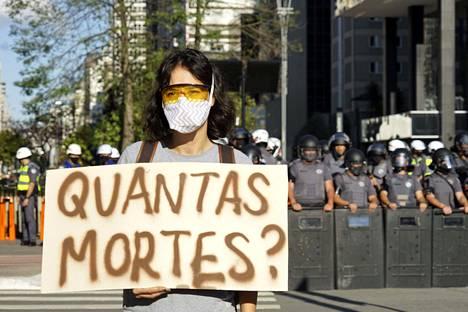 """""""Kuinka monta kuolemaa?"""" protestoija kysyi viikonlopun mielenosoituksissa São Paulossa. Presidentti Jair Bolsonaron koronavirustoimet ovat jakaneet Brasilian kansaa."""