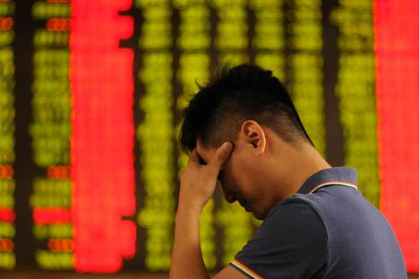 Kiinalaismies piteli päätään osakekurssitaulun edessä Hebein maakunnan Xingtaissa viime kesäkuussa, kun kurssi-indeksit olivat laskeneet päivän aikana useita prosentteja.