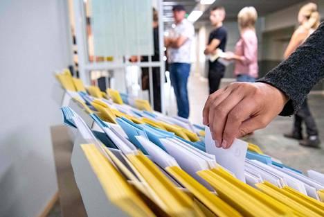 Äänestäjä poimi äänestyslipukkeen äänestyspaikalla Tomelillassa Ruotsissa sunnuntaina.