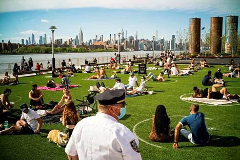 New Yorkin Brooklynin Domino Parkissa nautittiin kevätauringosta poliisin valvonnassa toukokuun puolivälissä.