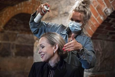 Meikkaaja Kaisa Pätila laittaa näyttelijä Anu Sinisalon hiuksia Johanneksenkirkossa. Myös Pätilällä on maski koronatartuntojen välttämiseksi.