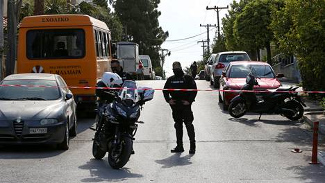 A police officer blocks the road where Greek journalist George Karaivaz was fatally shot in the Alimos suburb of Athens, Greece, April 9, 2021. REUTERS/Costas Baltas - RC2ESM9UMIWU