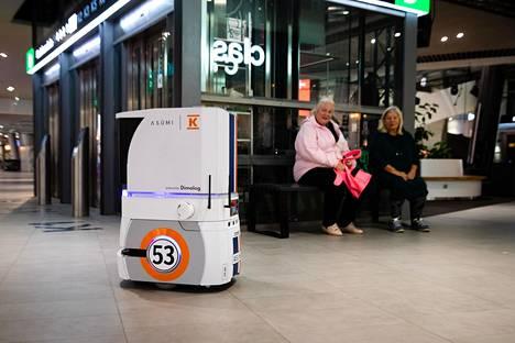 Robotti kulkee kauppakeskuksen asiakkaiden ohi matkallaan Majakan asuntoihin.