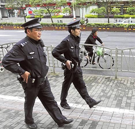 Aseistautuneet poliisit partioivat kadulla Shanghaissa sunnuntaina.