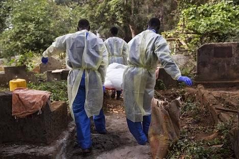 Punaisen Ristin työntekijät kantoivat ebolaepidemian uhria haudattavaksi Guinean Conakryssa tammikuussa 2015.