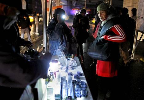 Nainen kyseli taskulamppujen hintaa Sandy-myrskyn jälkeen New Yorkissa.