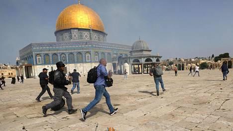 Israelilaispoliisi juoksee kameramiehen perässä Al-Aqsan moskeijalla levottomuuksien aikan.