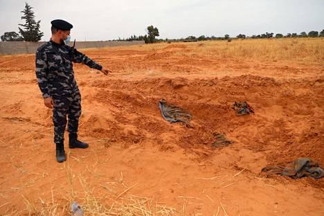 Libyan kansainvälisesti tunnustetun hallituksen joukkojen sotilas osoitti sormellaan paikkaa, jossa kerrotaan olleen joukkohauta.