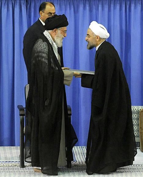 Iranin suurajatolla Ali Khamenei (vas.) antoi lauantaina virallisen hyväksyntänsä Hasan Ruhanin (oik. ) presidentiksi nousemiselle. Neljän vuoden kaudelle valittu Ruhani sai kesäkuun vaaleissa hiukan yli 50 prosenttia äänistä.
