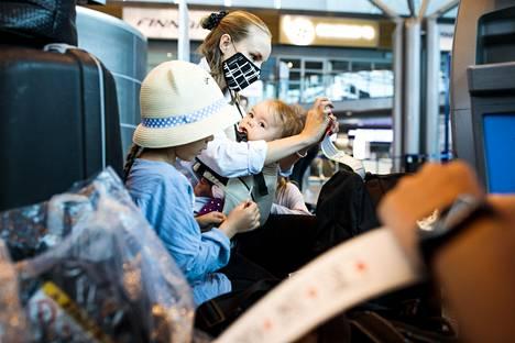 Iira Savikko kiinnittää matkalaukkuihin check in -automaatin tulostamia nauhoja sylissään Saga. Vasemmalla isosisko Isla ja äidin takana Aava.