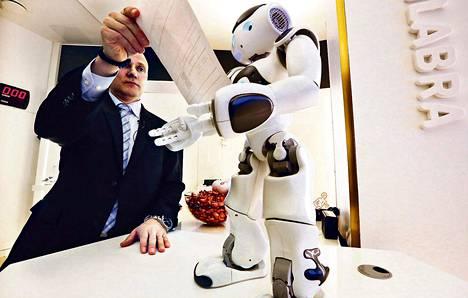 Tuotekehitysjohtaja Mika Kivimäki OP-Pohjolasta näyttää laskun pankkirobotille. Se lukee kameranäöllään laskun koodin. Ajatuksena on, että asiakkaat voisivat esimerkiksi maksaa laskujaan robotin avulla.