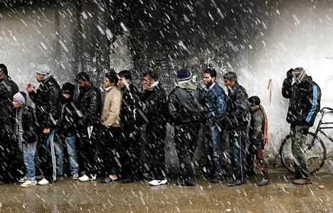 Miehiä jonottamassa lumisateessa leipää Al Qusayrissa, viiden kilometrin päässä Homsista.