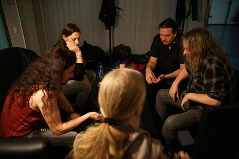 Keyboardist Tuomas Holopainen (left), singer Floor Jansen, bassist Marko Hietala, guitar technician Antti Toiviainen and multi-instrumentalist Troy Donockley kill time by playing a card in the back room.