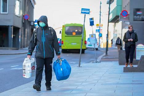 Norjalaismies kulki hengitysuojalla varustautuneena ostoksilla Oslossa 13. maaliskuuta.