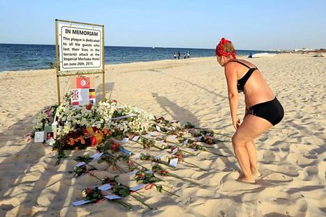 Turisti katseli viime kesäkuussa kylttiä, joka oli pystytetty vuotta aiemmin tehdyn iskun tapahtumapaikalle Tunisiassa uhrien muistoksi. Iskun tapahtumista valmistui selvitys Britanniassa tiistaina.