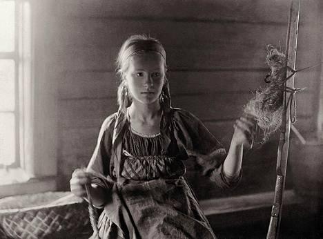 """Kaunis Toarie. """"Valokuvaaja Into Konrad Inha (1867–1930) vietti kesän 1894 Vienan Karjalassa; kylissä, joista Lönnrot oli kerännyt keskeisen osan Kalevalan runoutta. Uhtualla hän kuvasi kylän kauneimmaksi kehutun tytön, noin 15-vuotiaan Toarien, kehräämässä värttinällä. Inhalla on ollut valtava vaikutus siihen, miten Karjala on hänen jälkeensä nähty ja miten sitä on myöhemmin valokuvattu."""""""