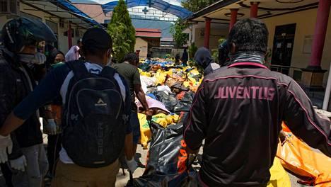 Pelastusmiehet kantavat tsunamin ja maanjäristyksen uhreja ruumiiden tunnistamispaikalle Palussa.