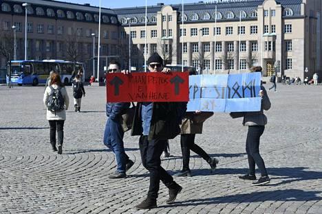 Koronaviruksen leviämisen estämiseksi säädettyjä rajoituksia vastustavia mielenosoittajia Rautatientorilla Helsingissä 18. huhtikuuta 2021.