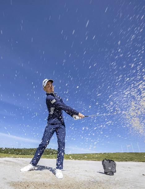 Kim Koivu treenaa hiekkalyöntejä bunkkerista, josta pallo nousee kevyesti.