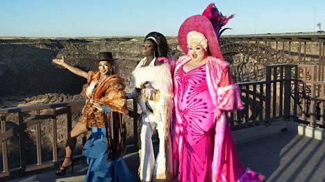 We're Here -sarjan juontajat  Shangela Laquifa Wadley (vas.), Caldwell Tidicue eli Bob the Drag Queen ja Eureka O'Hara matkustavat Yhdysvaltojen halki ja kouluttavat osallistujia dragesityksiin.