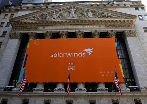 Solarwindsin logoa kantava lakana New Yorkin pörssin seinässä lokakuussa 2018. Kuva on otettu, kun Solarwinds järjesti pörssilistautumiseensa liittyvän osakeannin.