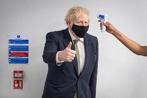 Britannian pääministeri Boris Johnson näytti peukkua ruumiinlämpönsä mittauksessa Chase Farmin sairaalassa Pohjois-Lontoossa maanantaina.