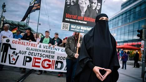 Maahanmuuttoa ja islamia vastustavan Pegida-liikkeen mielenosoituksen kärjessä Dresdenissä kulkee niqabiin pukeutunut hahmo, joka on asetellut kätensä samalla tavalla kuin Saksan liittokanslerilla Angela Merkelillä on tapana. Merkel on Pegidan maalitauluna myös mielenosoittajien kylteissä.
