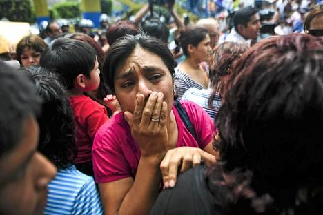 Omaiset surivat vieroitusklinikan tulipalon uhreja Limassa lauantaina.