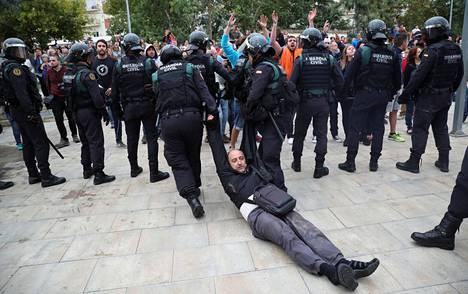 Mellakkapoliisit raahasivat miestä äänestyspaikan ulkopuolelta, jossa he ottivat yhteen itsenäisyysmielisten kanssa.