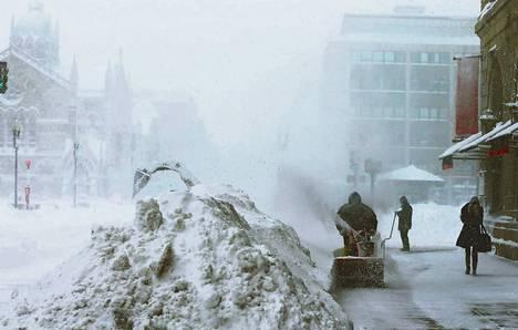 Huoltomies puhdisti lumilingolla jalkakäytävää Bostonissa lauantaina.