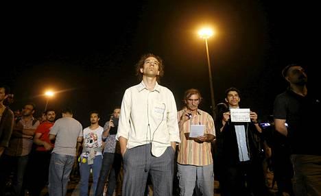 Erdem Gunduz (kesk.) seisoi äänettömässä protestissa Taksim-aukiolla varhain tiistai-aamuna.
