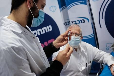 Sairaanhoitaja rokottaa vanhusta Jerusalemissa Israelissa. Noin miljoona israelilaista oli uudenvuodenaattoon mennessä ehtinyt saada ensimmäisen annoksen Pfizer-Biontechin rokotetta.