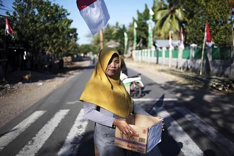 Nainen keräsi rahaa maanjäristyksen uhreille Lombokin saarella Indonesiassa torstaina.