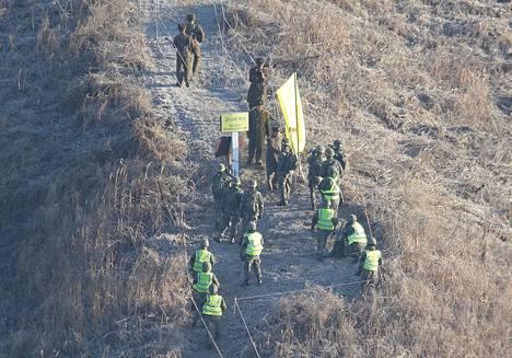 Pohjoiskorealainen ja eteläkorealainen sotilas kättelivät maidensa raja-alueella keskiviikkona.