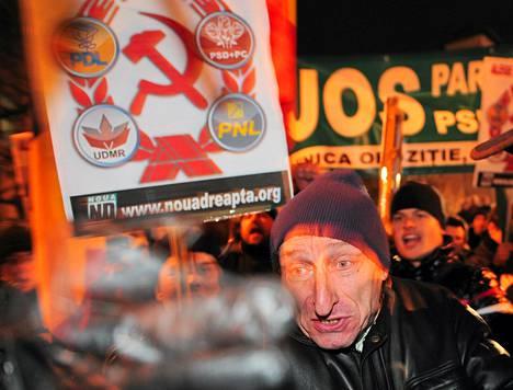 Parlamenttipuolueiden logot koristivat kommunistisen puolueen tunnusta mielenosoituksessa Romaniassa torstai-iltana.